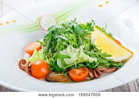 Seafood salad with mussels squids octopus arugula lettuce and cherry tomatoes on wooden background close up. Mediterranean food