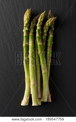 Bundle of fresh cut raw uncooked green asparagus vegetable on black stone board