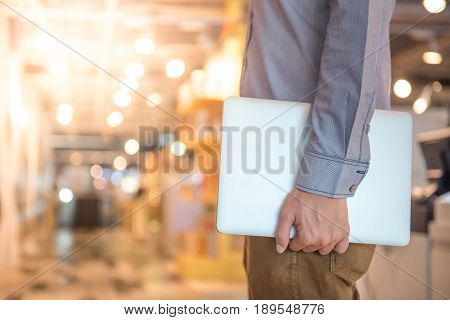 closeup of young male hand holding laptop computer in Department store with blurry light and bokeh effect in the background. Startup Business and digital nomad lifestyle concepts