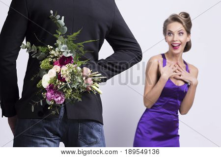 Man brings flowers to woman and hiding them behind back womanin evening dress is surprised and happy