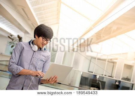 Young Asian business man dressed in casual style working with his laptop computer. Digital nomad in co working space modern IT lifestyle with work life balance concept.