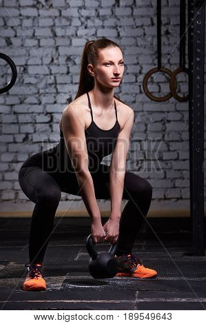 Young athletic woman exercising with kettlebell while being in squat position against brick wall. Sporty woman in the black sportwear, t-shirt, leggings and sporty shoes. Cross fit hard work. Healthy lifestyle.