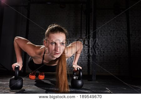 Young sporty woman doing push-ups exercise with kettlebell against brick wall. Close-up photo of beautiful woman. Sporty woman in the black sportwera, t-shirt, leggings and sporty shoes. Healthy lifestyle.