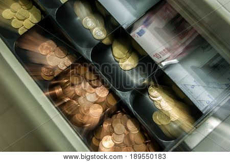 coins appearing to come out of a cash register loosing money
