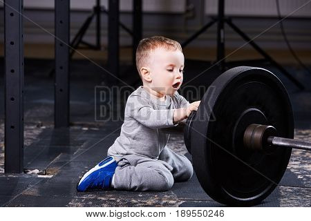 Little cute boy in sportwear sitting on the floor at the gym and looking on the barbell. Sporty child in the grey sportwear and blue sportive shoes. Child rearing in the healthy lifestyle.