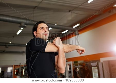 Young sportsman standing indoor and stretching triceps before gym workout. Athlete man in the black sportwear, t-shirt. Horizontal photo. Healthy lifestyle.