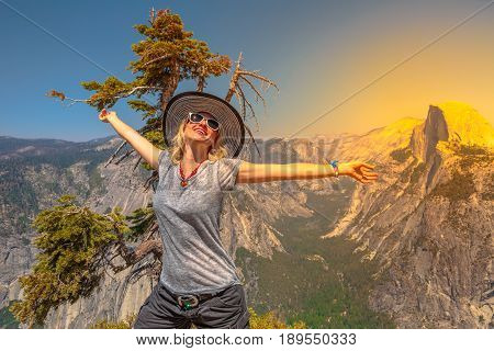 Woman freedom at Glacier Point, Yosemite National Park, California, USA.Happy tourist enjoying the view of the Half Dome from Glacier Point overlook. Sunset beautiful panorama. Summer holidays concept