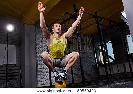 Young athletic man doing exercises in cross fit gym while crouching on two legs on the kettlebell. Sportsman in the sportwear, yellow t-shirt, shorts and sporty shoes. Portrait of smiling sportsman. Healthy lifestyle.