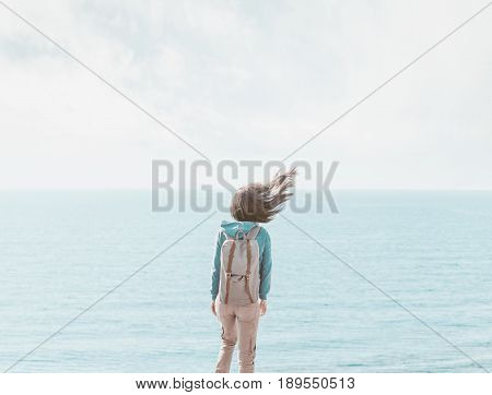 Traveler young woman with backpack standing on background of sea in windy weather her hair fluttering in the wind rear view.