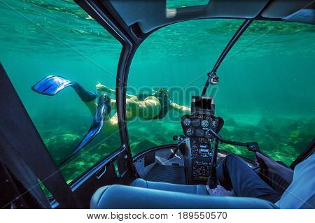 Underwater submarine ship following a woman in apnea swimming in tropical turquoise sea of Racha Noi, Phuket in Thailand. cockpit interior view