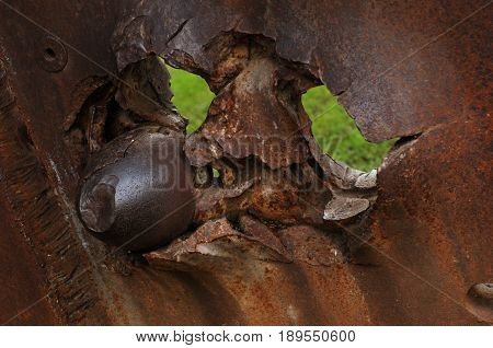 rusted metal plate with a canon bullet and holes of bullets part of a sunk ship rusted metal background
