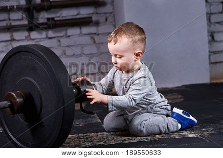 Little sporty boy in the grey sportwear looking and touching at thebarbell against brick wall in the gym. Sporty child in the bright blue sportive shoes. Rearing child in the healthy lifestyle.