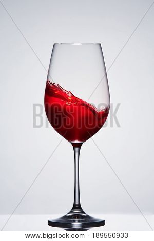 Moving red wine in the elegant wineglass standing against light background with reflection. Wave of the wine. Concept of the luxury lifestyle. Celebration of important dates. Sommelier and tasting.