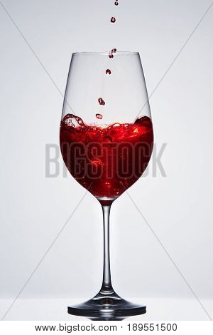 Brightly red wine poured in the fragile pure wineglass standing against light background with reflection in down. Bubbles and splashing. Luxury lifestyle. Celebration and relaxation. Viticulture, grapes and winery. Vertical photo.