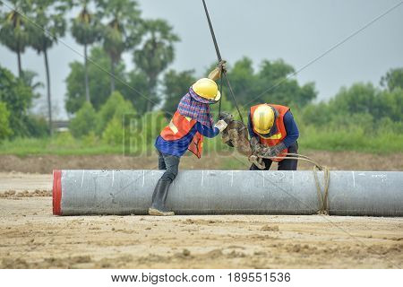 worker up lift concrete span pile by cable in construction site