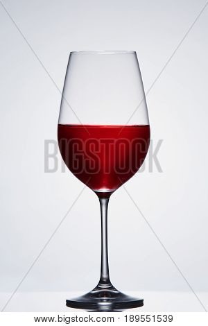Fragile elegant wineglass of red wine standing against light background. Concept of the luxury lifestyle, celebration and relaxation. Sommelier and degustation. Viticulture, winery and grapes. Vertical photo.