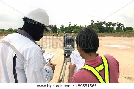 Construction engineer hodling construction drawing and smart tablet with foreman worker checking construction site for new Infrastructure construction project
