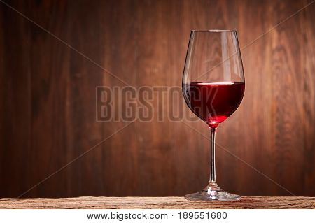 Red wine in the pure elegant wineglass standing on a wooden stand against wooden background. Natural material and product. Luxury lifestyle. Sommelier and tasting. Viticulture, grapes and winery. Horizontal photo.
