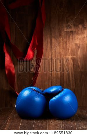Boxing background with blue gloves and red bandage on wooden table against wooden background. Vertical photo of the sportwear and sportive accessories. Power and energy. Concept of the sportive healthy lifestyle.