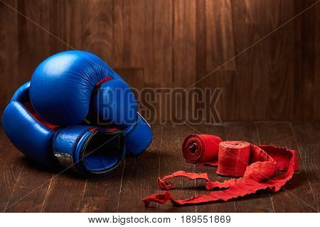 Pair of blue boxing gloves with two rolls of hand bandage on wooden background. Bright sportwear and accessories on wooden wall background. Power, energy and victory. Concept of the sportive healthy lifestyle.