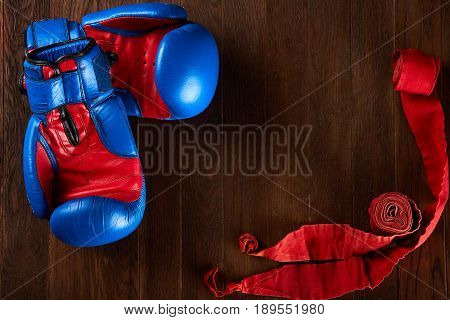 Sport background with blue and red gloves and red bandage on wooden background. Horizontal photo, top view and close-up. Sportive exercise and training. Colorful sportwear and accessories. Concept of the sportive healthy lifestyle.