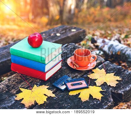 Books and a cup of hot coffee with cinnamon on the table in the forest at sunset. Vintage style. Back to school. Education concept. Beautiful autumn background. Weekend in the park.