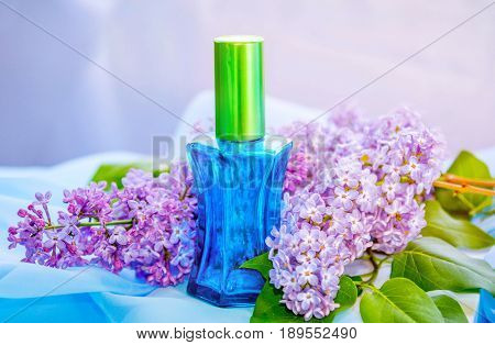 Blue glass perfume bottle with drops of water on a white box and  beautiful  fresh lilac flowers and textile