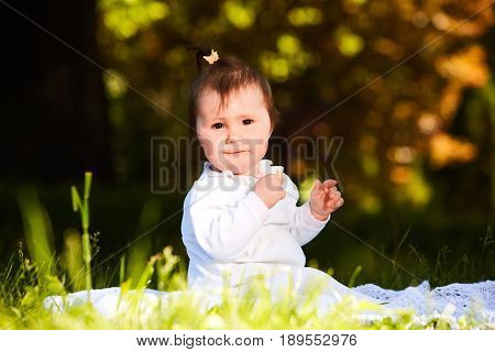 Cheerful baby girl sitting on the green grass in the city park at warm summer day. Cute little girl in the white beauty dress. Horizontal photo. Sunshiny day in outside. Concept of the happy babies.