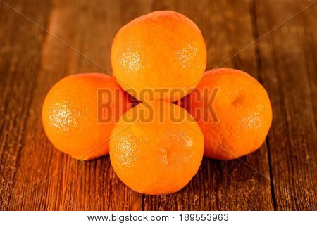 Group of orange tangerines on a wood background