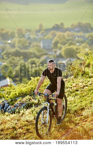 Extreme mountain cyclist riding bike on rocky trail at sunshiny day. Vertical photo. Young sportsman in the black sportwear and with sportive shoes. Beautiful landscape like a background. Concept of the healthy and active lifestyle.