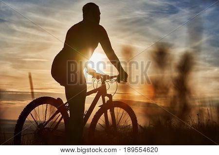 Silhouette of cyclist standing with mountain bike on the hill at sunset. Young sportsman in the sportwear. Extreme travelling in the countryside. Beautiful landscape like a background. Concept of the healthy and active lifestyle.