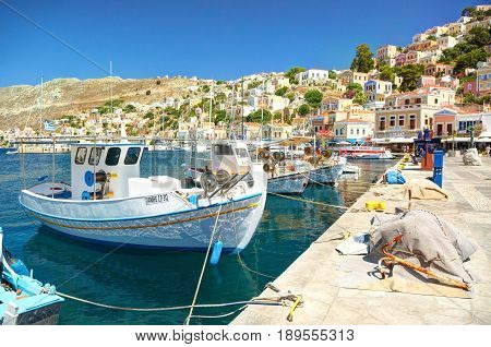 SYMI ISLAND, GREECE, JUNE 25, 2013: View on beautiful classic old piscatory sea boats ships, Greek sea port, gingerbread houses hills, tourists, and blue water bay. Rhodes retro boats ships yachts