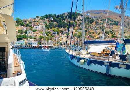 SYMI ISLAND, GREECE, JUNE 25, 2013: View on beautiful classic sea ocean yachts, Greek sea port, houses on island hills, tourists, blue water bay. Classic white yachts at pier. Greece islands tours