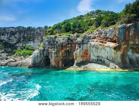Beautiful view on Blue caves and blue water of Ionian sea on Island Zakynthos in Greece and sightseeing points on the rock. Boat trip from Agios Nikolaos port. Best famous sightseeing tours boat trips