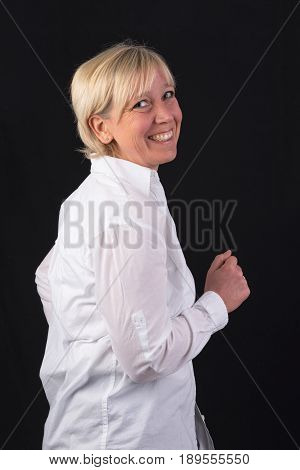 beautiful caucasian mature woman in white shirt, dancing - photograph on black background