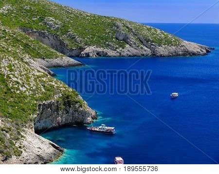 View on amazing bay, boats and ships with swimming people in Ionian Sea blue water near to Blue Caves. Famous sightseeing point. Greece holidays vacations tours tourism. Greece islands boat tours