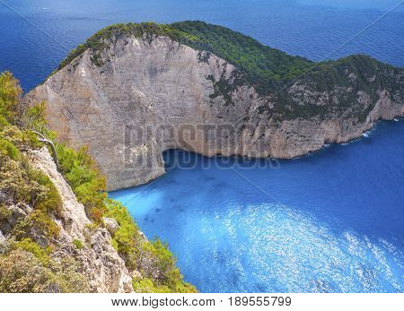 Beautiful view on Navagio rock of shipwreck beach sightseeing boat, blue water of Ionian Sea, blue caves from Navagio view point. Boat trips travel to shipwreck sand beach. Greece, Island Zakynthos