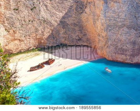 View on Shipwreck beach in amazing bay, boats and ships with swimming people in Ionian Sea blue water Blue Caves. Greece islands Zakynthos Navagio beach sightseeing holidays vacations tours boat trip
