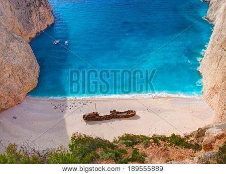 Beautiful view on Shipwreck beach in amazing bay, boats and ships with swimming people in Ionian Sea blue water, Blue Caves shipwreck beach. Greece Island Zakynthos holidays. Navagio beach view point