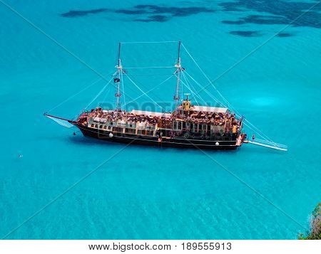 Pirate corsair style boat ship in amazing Greece island bay with swimming people, beach in Ionian Sea blue water, Greece islands holidays vacations tours. Xigia beach, Zakynthos island. Best holidays