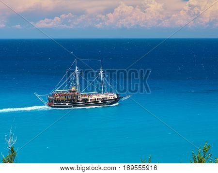 Running pirate corsair style boat ship in amazing Greece island bay with swimming people, beach in Ionian Sea blue water, Famous Greece islands holidays vacations tours. Xigia beach, Zakynthos island