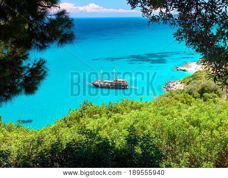 Trees frame beautiful view on amazing island bay with pirate corsair style boat ship, swimming people, beach in Ionian Sea blue water, Greece islands holidays, close to Xigia beach on Zakynthos island