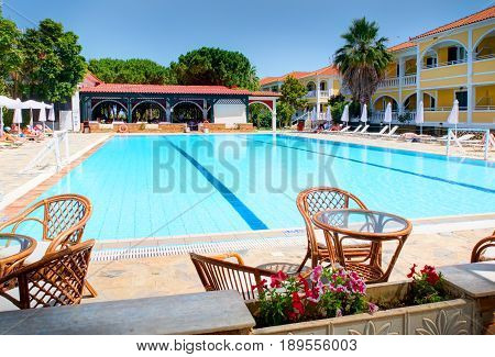 ZAKYNTHOS ISLAND GREECE, JUNE 06, 2016: View on hotel swimming pool bar, flowers, restaurant furniture chairs and tables, toasting tourists Greek hotel Royal Zante. Greece holidays vacation tours