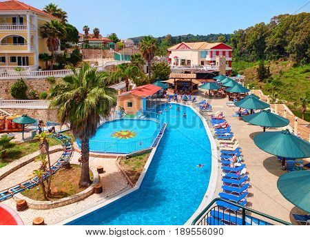 ZAKYNTHOS ISLAND GREECE, JUNE 06, 2016: View on hotel swimming pool bar restaurant, tourists, guests, aqua water park from water slides of Greek hotel Royal Zante. Greece holidays vacation on islands