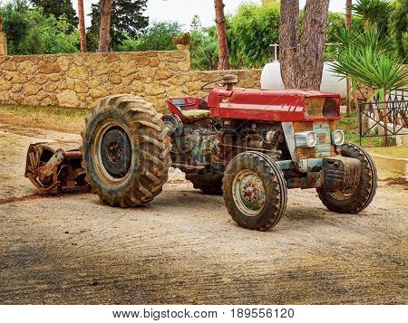 Old fashion antique worn rusted rural red four wheel tractor among green trees. Old agricultural industry machine crawler tractor farm vehicle. Abstract agricultural tractor rusted metal beast