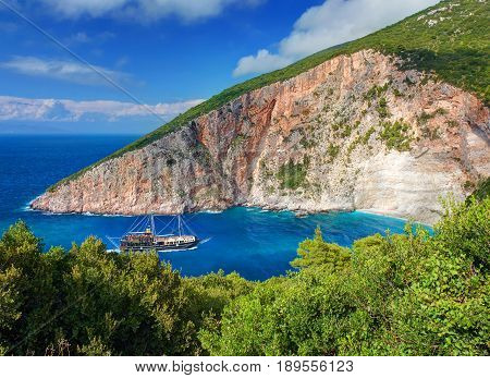 Pirate filibuster boat ship with tourists at Zakynthos blue caves Elation Sparto beach sea bay. Green sand stone rocks at Ionian Sea. Sand beach. Greece islands holidays vacations famous places tours poster