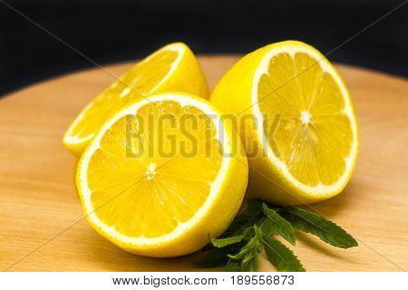 Half Of Lemon On A Wooden Board. Lemons  On A Wooden Background. Lemons. Fruits. Lemon Halves. Mint.