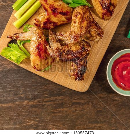 A square overhead photo of grilled chicken wings with celery and red tomato sauce, with a place for text