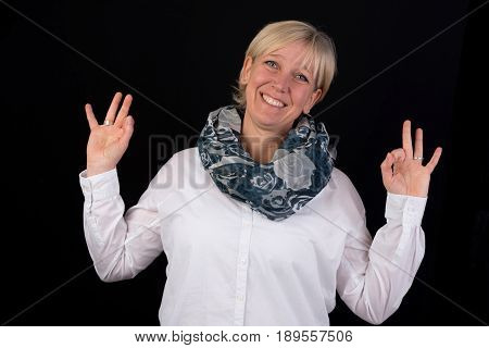 attractive blonde mature woman giving thumbs-up as positive signal - photograph on black background