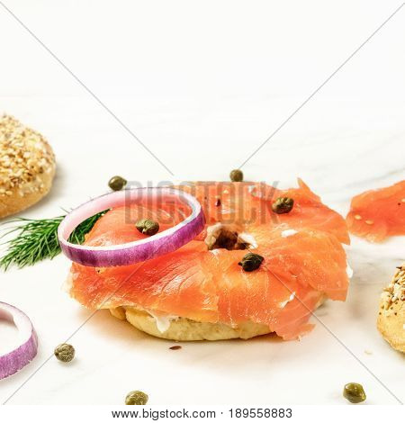 Bagel ingredients. Lox, purple onions, capers, dill, and the buns, shot on a white marble background in the process of making, with a place for text, square photo